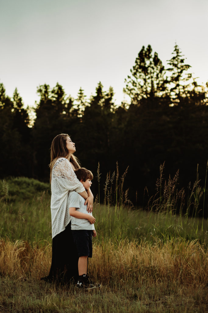 Family Photographer, mother holds son close as they stand in grass before a forest