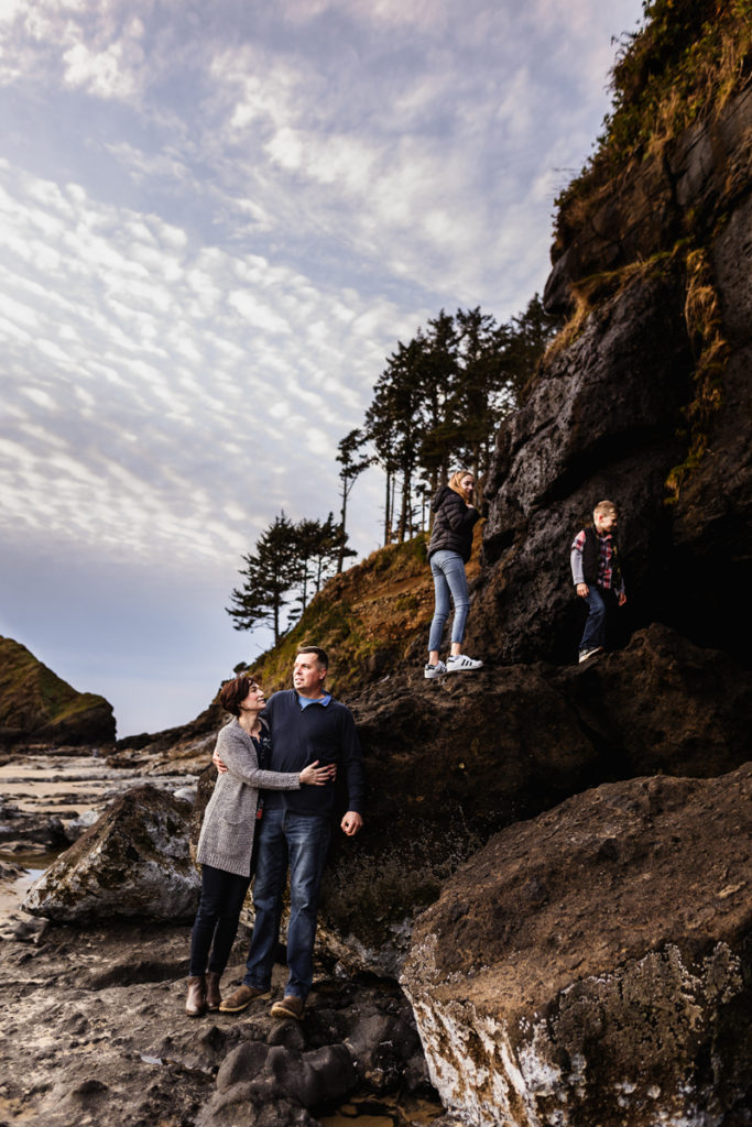 Family Photographer, Mom and dad embrace while kids climbing on beachside rocks