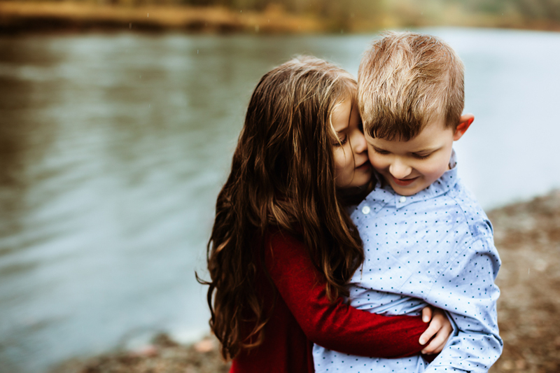 Family photographer, little girl hugs little boy as they sit on a lakeshore