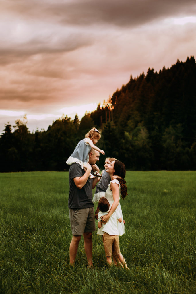Family Photography, young family all look to each other laughing in a grassy field near forest